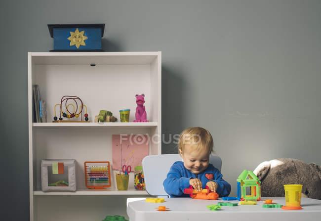 Bébé fille souriante jouant avec l'argile de modélisation dans la chambre des enfants — Photo de stock