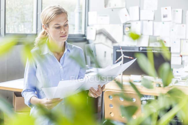 Mujer en la oficina trabajando en el plan con el modelo de turbina eólica sobre la mesa - foto de stock