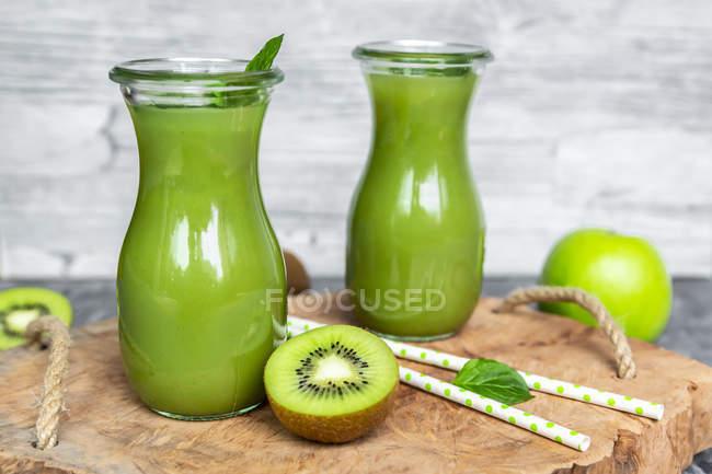 Deux bouteilles en verre de smoothie au kiwi aux pommes — Photo de stock