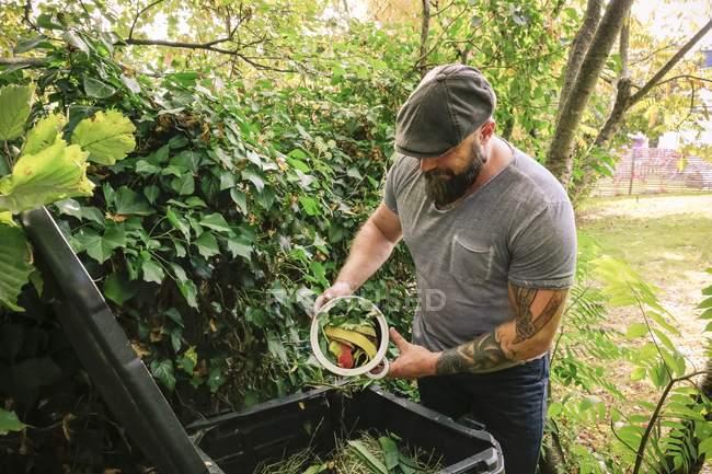 Homme mûr jetant des restes de cuisine sur un tas de compost — Photo de stock