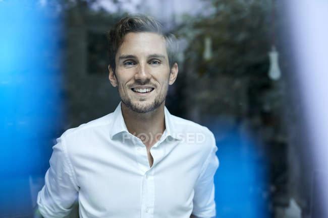 Ritratto di giovane uomo d'affari sorridente dietro il vetro della finestra — Foto stock