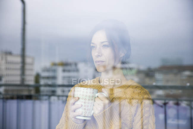 Sad woman standing at the window, drinking tea — стоковое фото