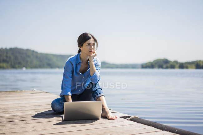 Frau arbeitet an einem See mit Laptop auf einem Steg — Stockfoto