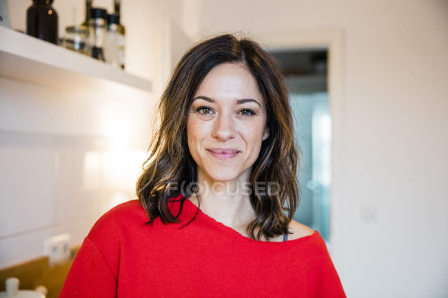 Portrait of a confident woman wearing red pullover — Stock Photo