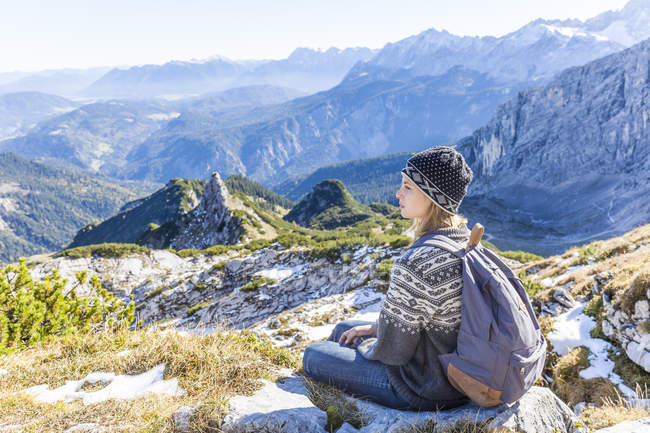 Germany, Garmisch-Partenkirchen, Alpspitze, Osterfelderkopf, female hiker on viewpoint looking at view — Stock Photo