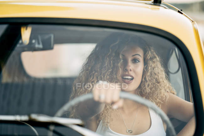 Portrait of surprised blond woman driving classic car — Stock Photo
