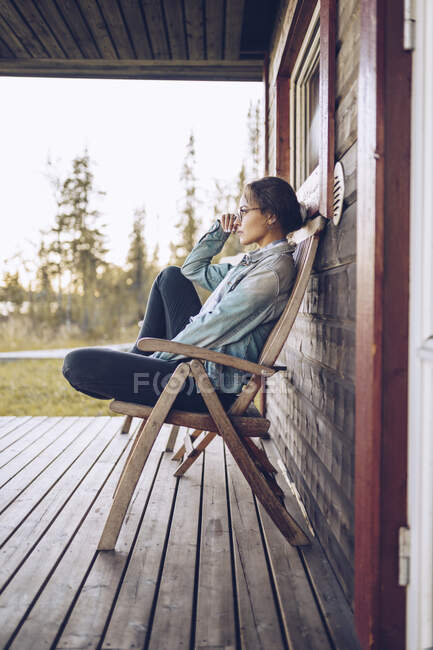 Sweden, Lapland, pensive young woman sitting on chair on veranda looking at distance — Stock Photo