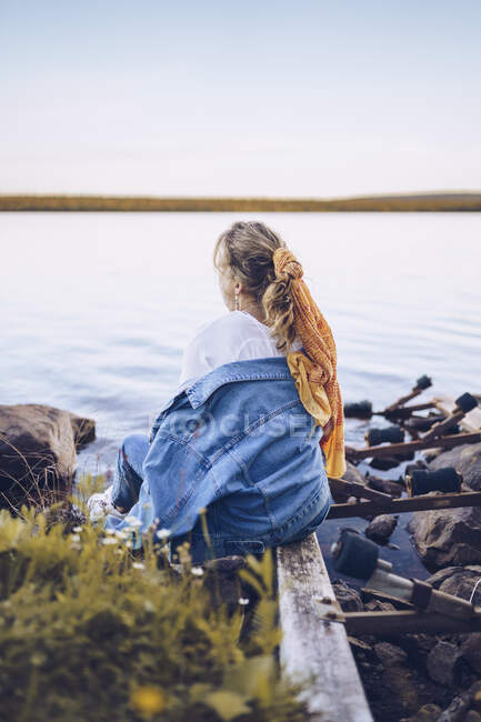 Sweden, Lapland, back view of young woman sitting at water's edge looking at distance — Stock Photo