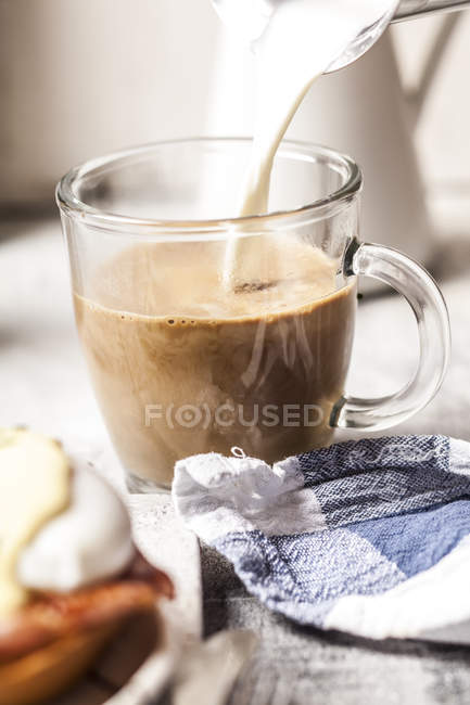 Pouring milk into a mug of coffee — Stock Photo
