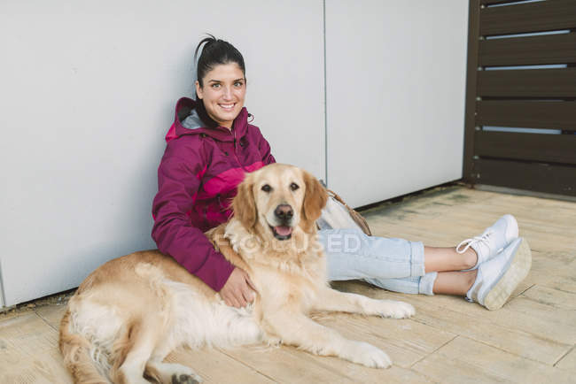 Портрет улыбающейся молодой женщины со своей золотистой собакой-ретривером, сидящей у стены — стоковое фото