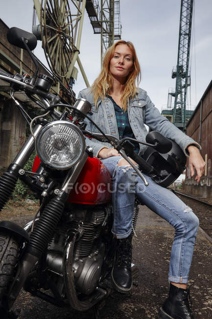 Portrait of confident young woman on motorcycle — Stock Photo