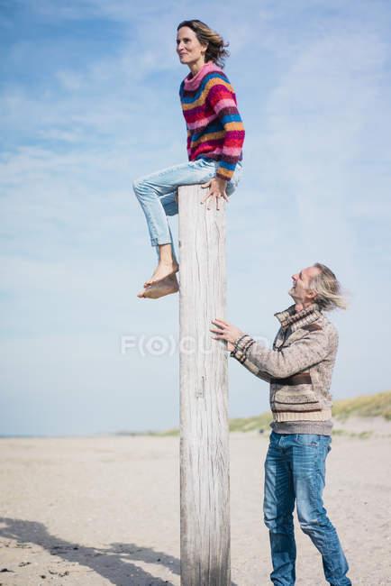 Mature man helping woman to climb a wood pole on he beach — Stock Photo