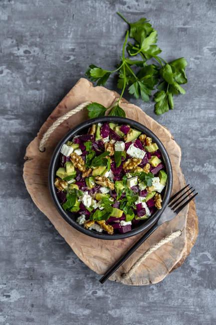 Чаша салату з буряком з авокадо, фетою, волоськими горіхами та петрушкою — стокове фото