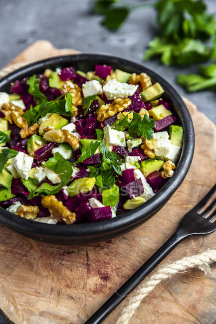 Bowl of beetroot salad with avocado, feta, walnuts and parsley — Stock Photo