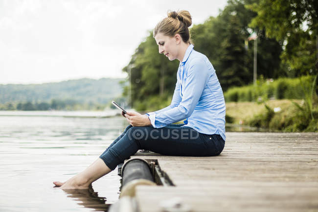 Frau sitzt auf Steg an einem See und mit Tablet — Stockfoto