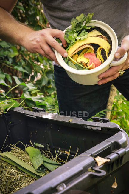 Partial view of Mature man discarding kitchen scraps on compost pile — Stock Photo