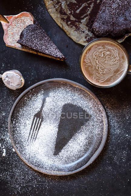 Impronta di una fetta di torta e una forchetta, fatta con zucchero a velo, tazza di caffè, torta al cioccolato — Foto stock