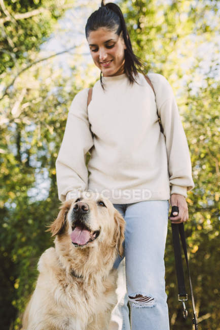 Sorridente giovane donna con il suo cane Golden retriever in un parco — Foto stock