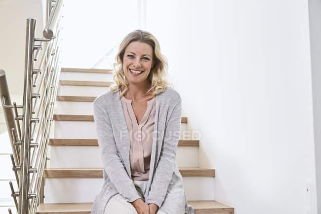 Портрет улыбающейся женщины, сидящей дома на лестнице — стоковое фото