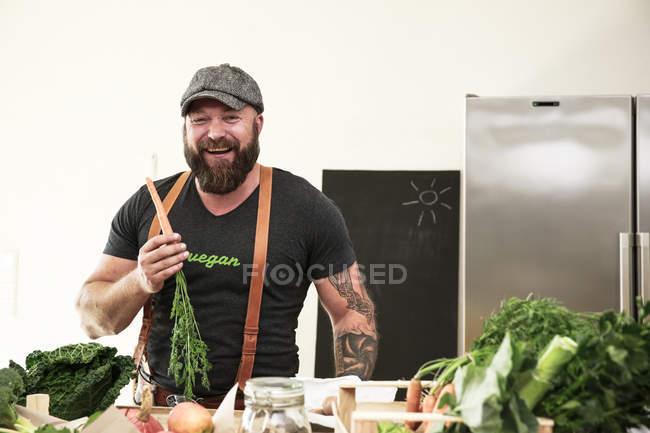 Cenoura da terra arrendada do homem do vegan em sua cozinha — Fotografia de Stock