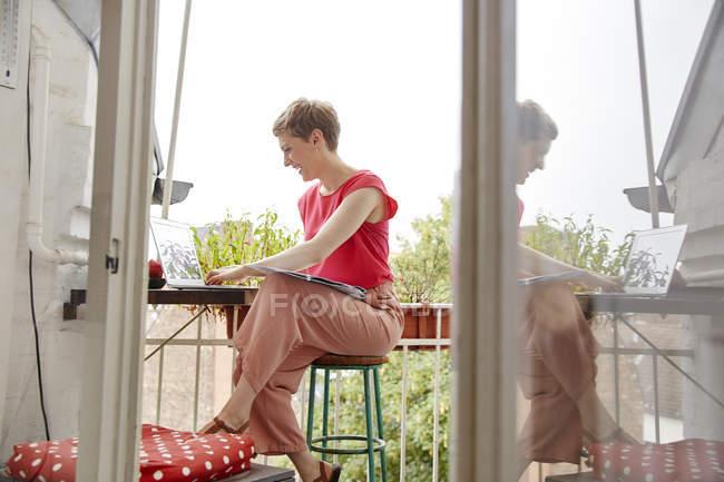Mulher feliz sentada na varanda em casa com laptop e mapa — Fotografia de Stock