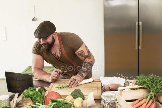 Uomo maturo che prova ricette vegetariane online, leggendo in laptop — Foto stock