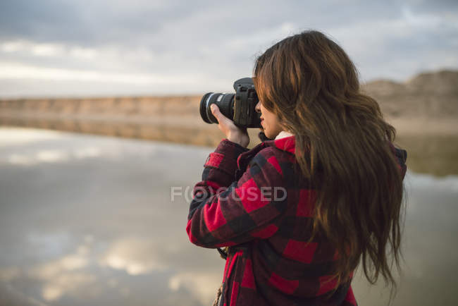 Young woman taking picture with camera on the beach — Stock Photo