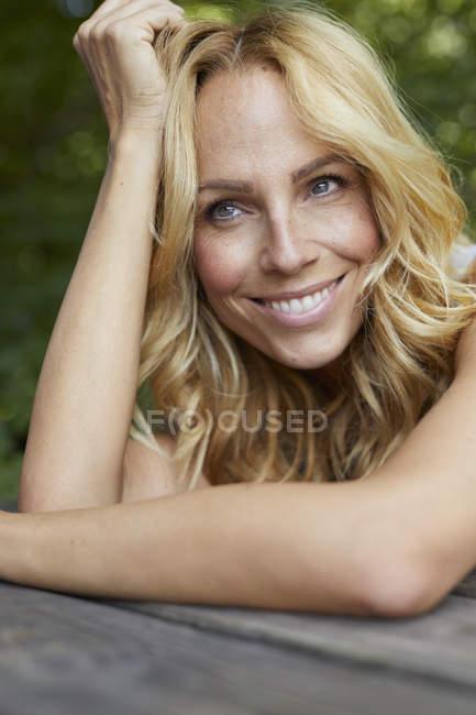 Retrato de mujer rubia sonriente con pecas al aire libre - foto de stock