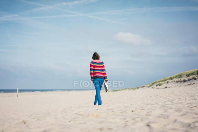 Пожилая женщина, гуляя босиком по пляжу — стоковое фото