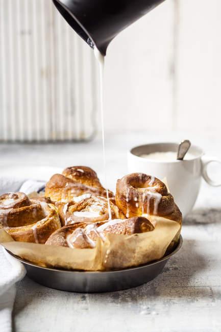 Garnishing home-baked cinnamon buns with icing sugar — Stock Photo