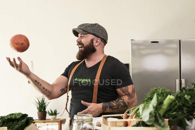 Homem do vegan que joga com uma abóbora em sua cozinha — Fotografia de Stock