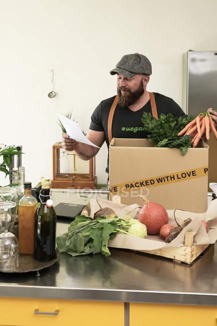 Зрелый человек с доставкой органических овощей в картон — стоковое фото
