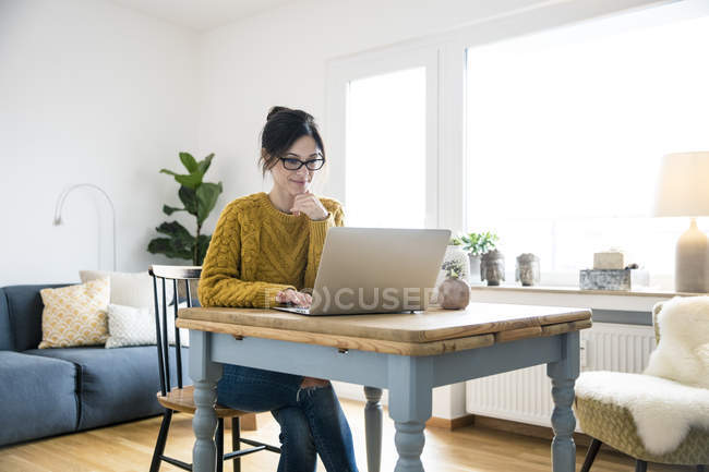 Woman sitting at table, using laptop — Stock Photo