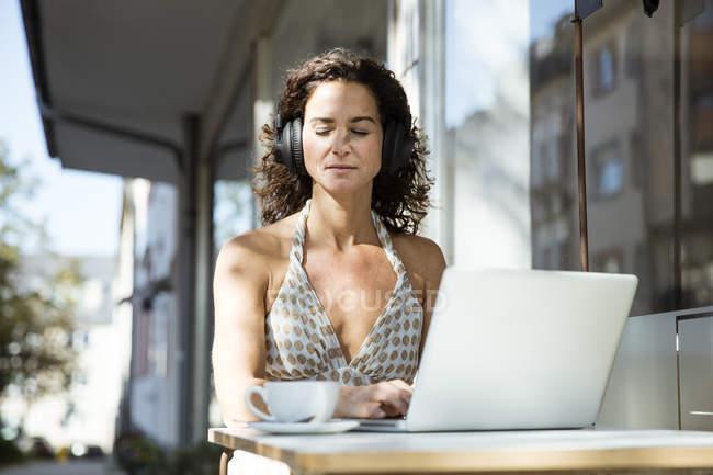 Frau sitzt im Café, trägt Kopfhörer, benutzt Laptop — Stockfoto