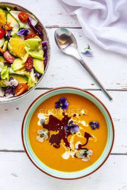 Bacia de salada misturada com as flores comestíveis e a bacia de sopa de abóbora creme decorada com flores comestíveis — Fotografia de Stock