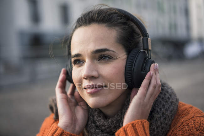 Portrait of smiling woman wearing listening music with cordless headphones in autumn — Stock Photo