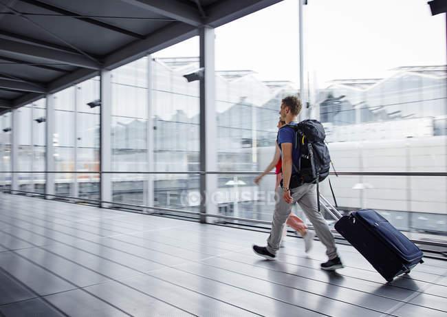 Coppia che cammina veloce in aeroporto — Foto stock