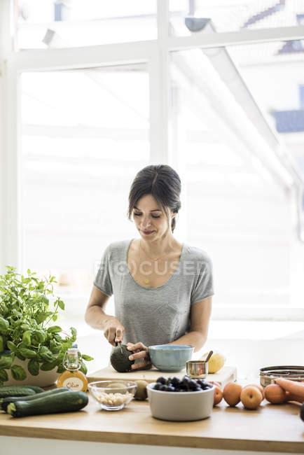 Mulher que prepara o alimento saudável em sua cozinha — Fotografia de Stock