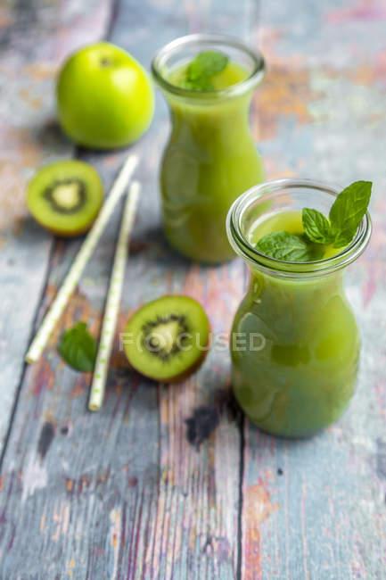 Due bottiglie di vetro di frullato di kiwi di mele — Foto stock