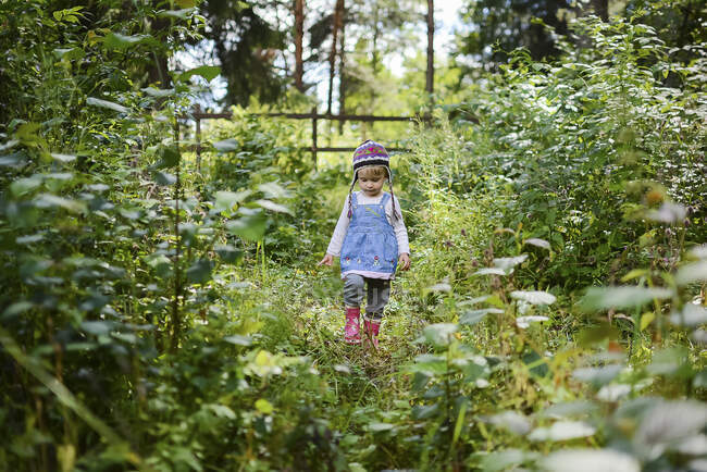 Little girl wearing knitted hat and denim shirt in nature — Stock Photo