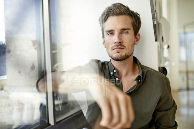 Portrait of serious young man sitting behind windowpane — Stock Photo
