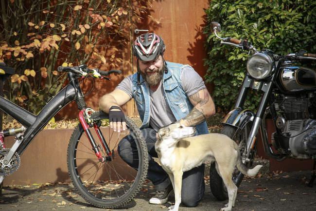 Улыбающийся мужчина с велосипедом, собакой и мотоциклом — стоковое фото