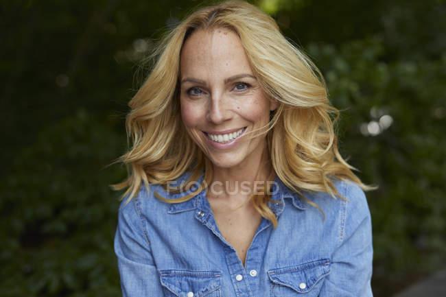 Porträt einer lächelnden blonden Frau im Freien — Stockfoto