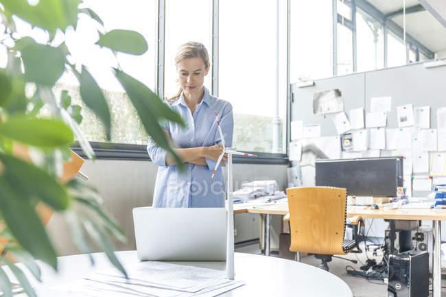 Женщина в офисе с планом, ноутбук и модель ветряной турбины на столе — стоковое фото