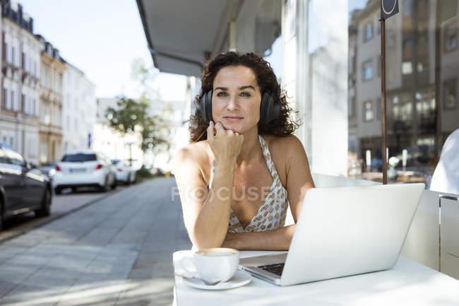 Reife Frau sitzt im Café, trägt Kopfhörer, mit Laptop — Stockfoto