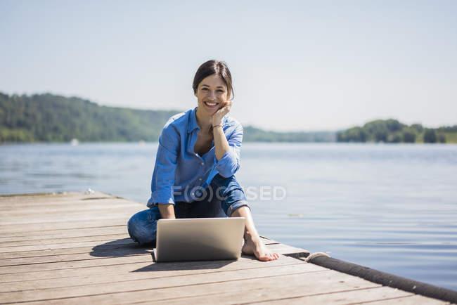 Літня жінка працює на озері, використовуючи ноутбук на пристані — стокове фото