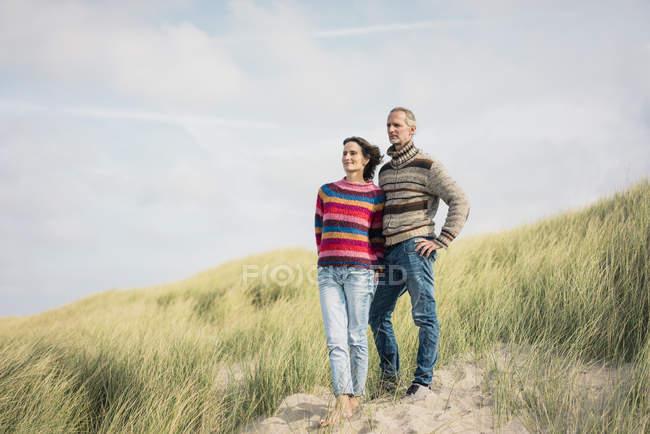 Зрелая пара, стоящая в дюнах, с оружием вокруг — стоковое фото