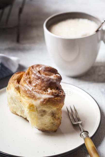 Panino alla cannella al forno casalingo con zucchero a velo e una tazza di caffè — Foto stock