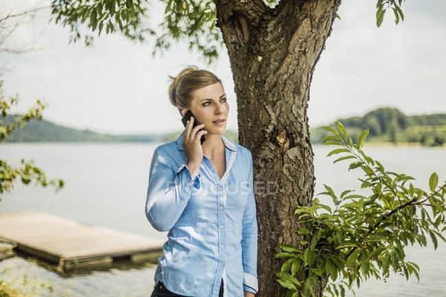Frau auf Handy an einem See — Stockfoto