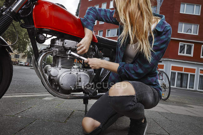 Young woman working on motorcycle — Stock Photo